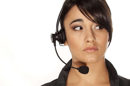 Young woman with headset looking to her left with a worried expression. Stock Photo
