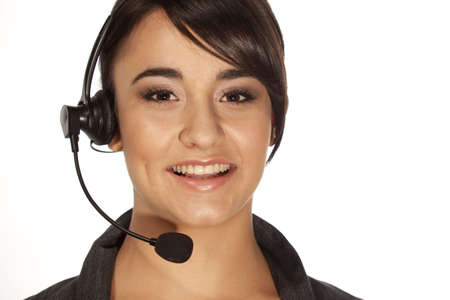 Young woman with telephone headset smiling at camera.