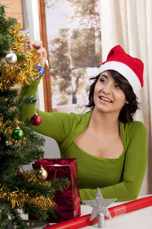 Gorgeous young woman decorating a Christmas tree, and wearing a Santa Hat.