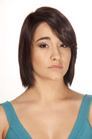 Young attractive woman with short hairstyle looking straight into camera on white background.