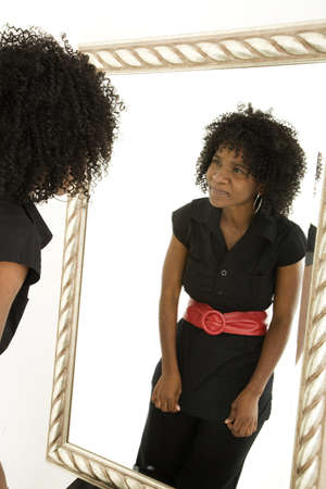 quizzical: Lady looking at herself in mirror with quizzical expression Stock Photo