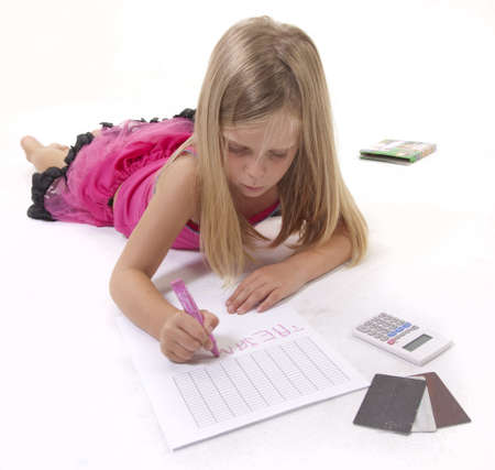 Little girl drawing on a spreadsheet with a crayon, surrounded by financial parephernalia.  photo