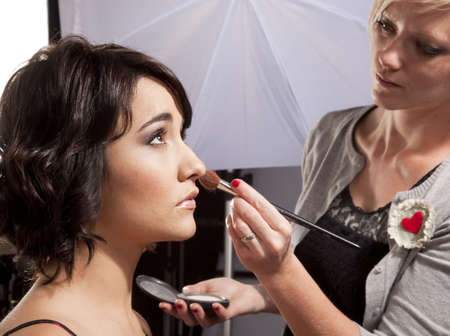 Make-up artist puttin makeup on model at a a photoshoot Stock Photo