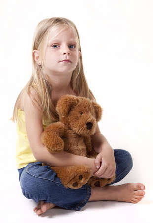Little girl with teddy bear looking sad away from camera.