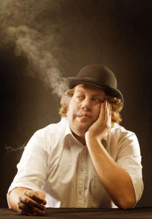 Vintage image of man in bowler hat smoking a cigarette, looking listless.