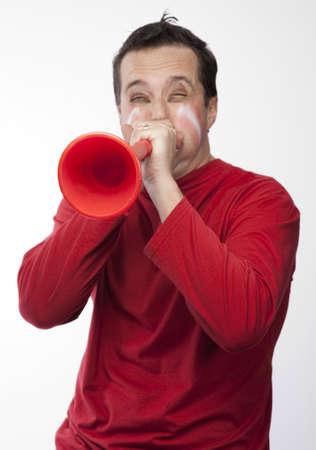 Sport supporter blowing vuvuzela on white background