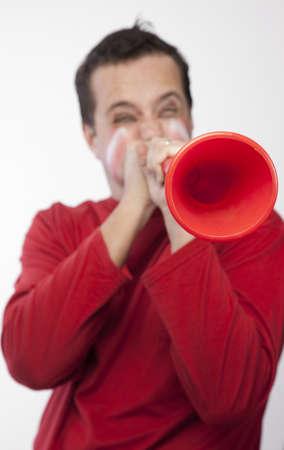 Man in red blowing vuvuzela