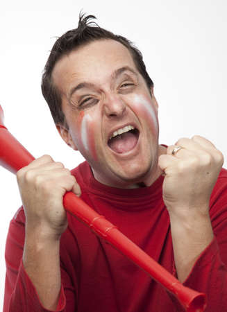 Excited fan of the red team holding a vuvuzela Stock Photo - 10772039