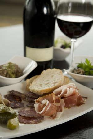 tapas españolas: Tapas y maridaje de vinos de color rojo en pequeños cuencos blancos en la mesa de noche. Foto de archivo