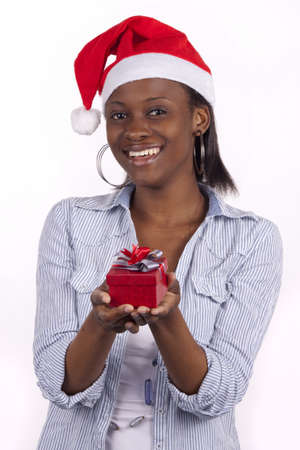 Young South African woman wearing a Santa hat and holding a present.
