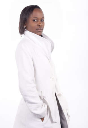 Gorgeous young South African woman in white coat on a white background.  photo