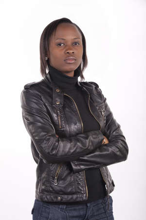 Young South African woman wearing black leather and a serious expression on a white background.  photo