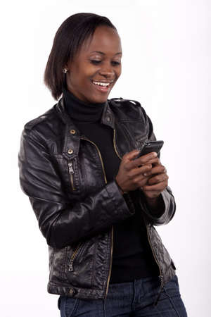 black sweater: Gorgeous young South African woman reading a surprising message on her phone. Stock Photo