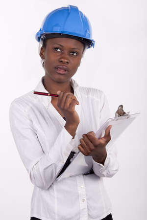 Young South African woman wearing a hard-hat, and making notes on a pad