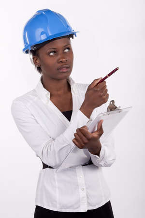quantity: Young South African woman wearing a hard-hat, and making notes on a pad