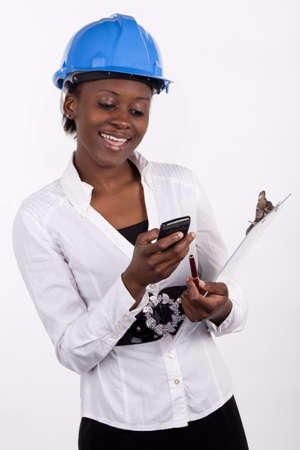 quantity surveyor: Young Engineering woman typing a text message on her phone  Stock Photo
