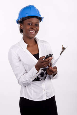 quantity: Young Engineering woman typing a text message on her phone  Stock Photo
