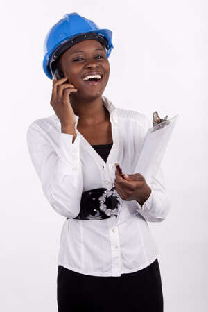 Laughing young woman in hard hat and holding a clipboard, and speaking on her phone