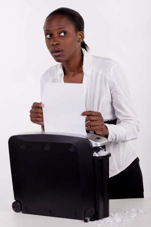 South African woman secretly shredding a document. Stock Photo