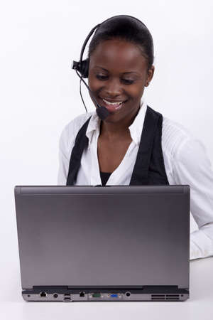 Woman with telephone headset and a laptop, serving a customer telephonically. Stock Photo
