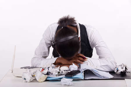 Young South African woman overwhelmed by work, telephones and stress.