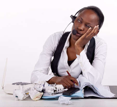 Young South African woman overwhelmed by work, telephones and stress. photo