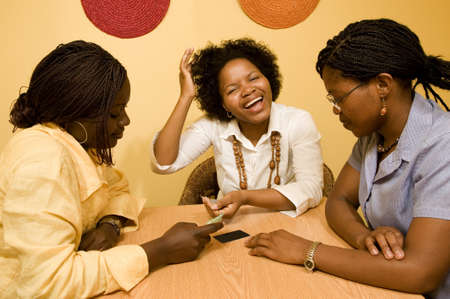 south african: 3 African women sitting at a table in discussion  Credit Cards are laid out on the table in front of them