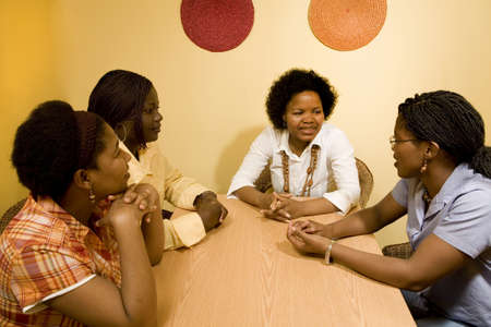 African women sitting at a table in discussion