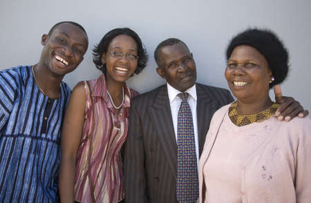 4 African people standing together against a wall with happy expressions  Thye look like family  Stock Photo