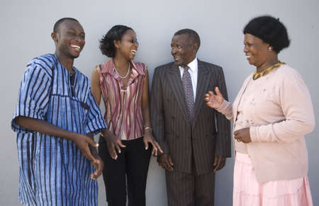 familia unida: 4 personas africanas de pie junto a una pared con expresiones felices Foto de archivo