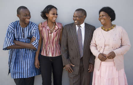 ebony: 4 African people standing together against a wall with happy expressions   Stock Photo