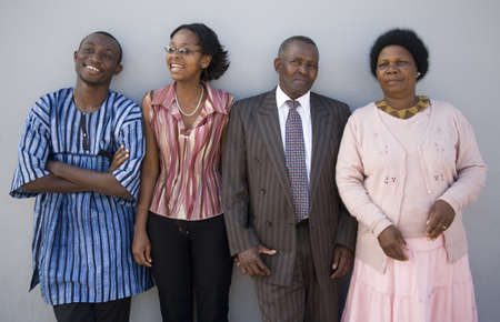 4 African people standing together against a wall  The younger ones look happy, the older ones serious