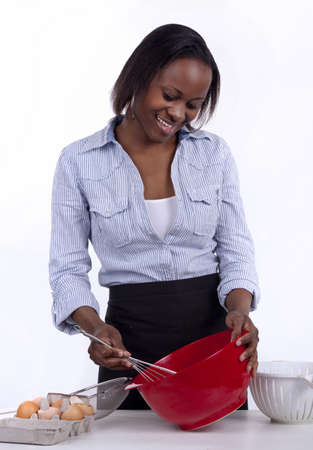 Young South African woman whisking egg in a red bowl  photo