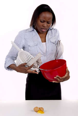 South African woman struggling with a mess she made in the kitchen. photo