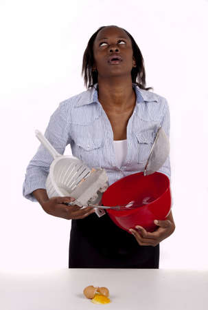 clumsy: South African woman struggling with a mess she made in the kitchen. Stock Photo