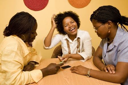 3 African women sitting at a table in discussion. Credit Cards are laid out on the table in front of them. Stock Photo
