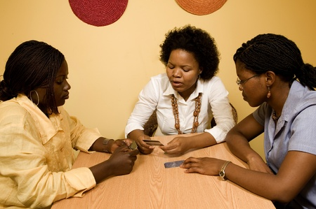 3 African women sitting at a table in discussion. They seem to be discussing credit cards laid out on the table Stock Photo