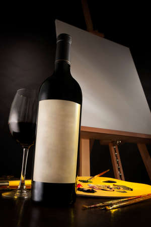 Bottle of good red wine, and a glass of wine, next to a palette, with paint brushes and a blank canvas in the background  Stock Photo