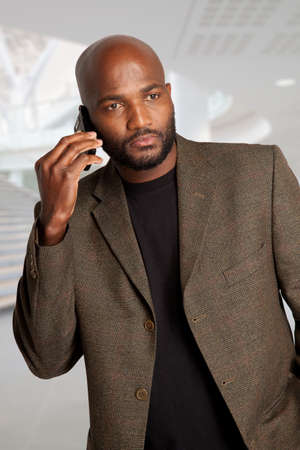 thirty something: Handsome South African male with a smart phone in a office building Stock Photo