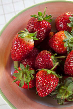 Bowl of strawberries closeup on a table, showing red color.