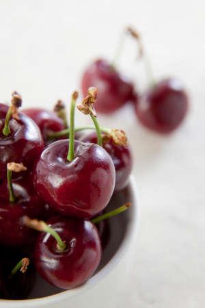 Organic Cherries in bowl on white background. Stock Photo
