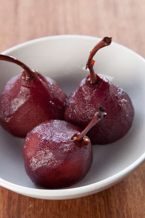 Pears poached in red wine in a white bowl