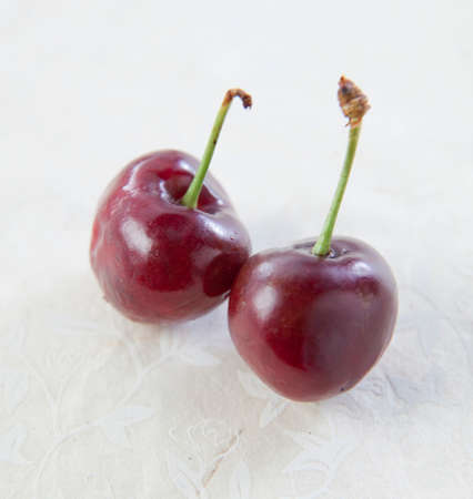 Two Organic cherries on a white background.