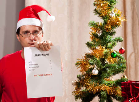 Caucasian man looking at the disastrous Xmas budget and expenses.
