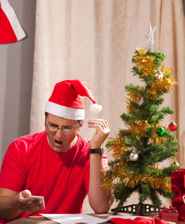 christmas debt: Caucasian man looking at the disastrous Xmas budget and expenses.