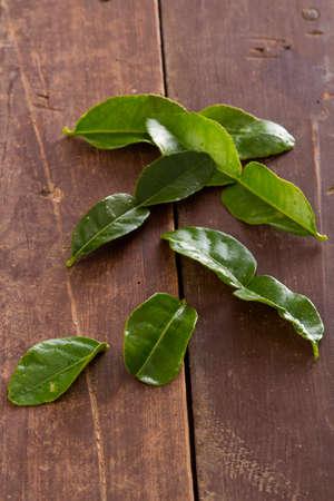 Kafir Lime Leaves on a rustic wood background.