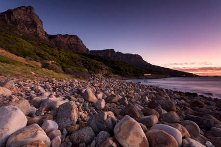 Pebble beach at Camps Bay area, Cape Town, with car headlights in the background. Stock Photo