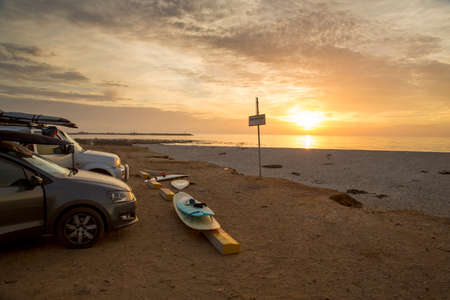 Surfboards and cars at the beach, after a good days surf on South Africas West Coast, at Lamberts Bay, Yo-Yo Bay.