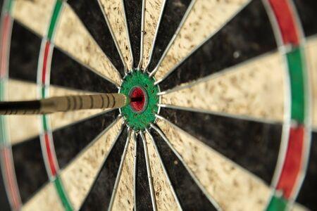 Darts hitting a bulls eye for a perfect score