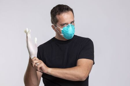 a Man in a surgical mask putting on latex gloves.